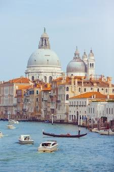 Basílica de santa maria della salute, veneza, itália. paisagem do grande canal com gôndolas e barcos.
