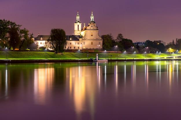 Basílica de são miguel arcanjo com reflexo no rio à noite, cracóvia