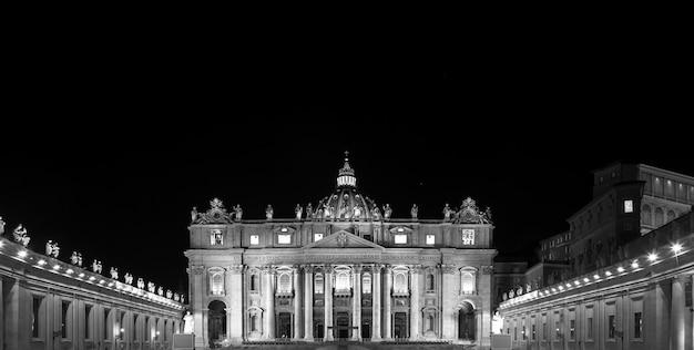 Basílica papal de são pedro na cidade do vaticano iluminada à noite, projetada por michelangelo e bernini