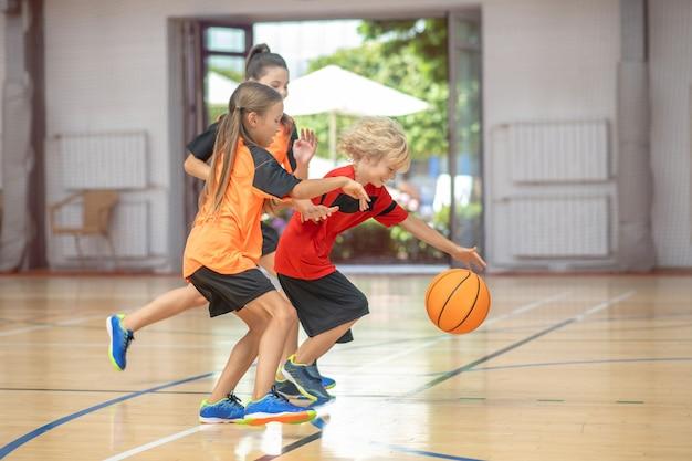Basquetebol. crianças em roupas esportivas brilhantes jogando basquete juntas e animadas