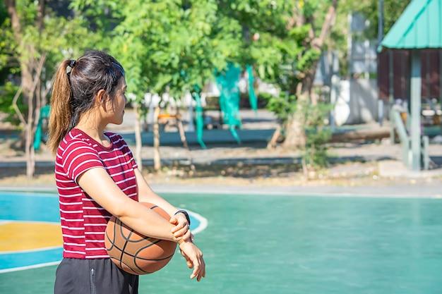 Basquetebol de couro à disposicão de uma mulher que veste uma árvore do borrão do fundo do relógio no parque.