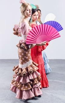 Bastante de três jovens flamencos em vestido lindo.