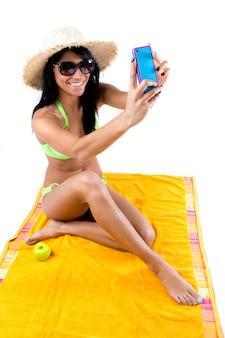 Bastante jovem com biquíni verde tomando selfies com seu telefone inteligente