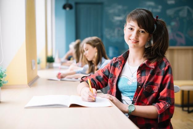 Bastante jovem sentado na mesa na sala de aula