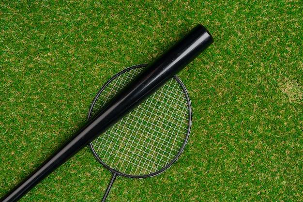 Bastão de beisebol e raquete de badminton na grama, vista superior
