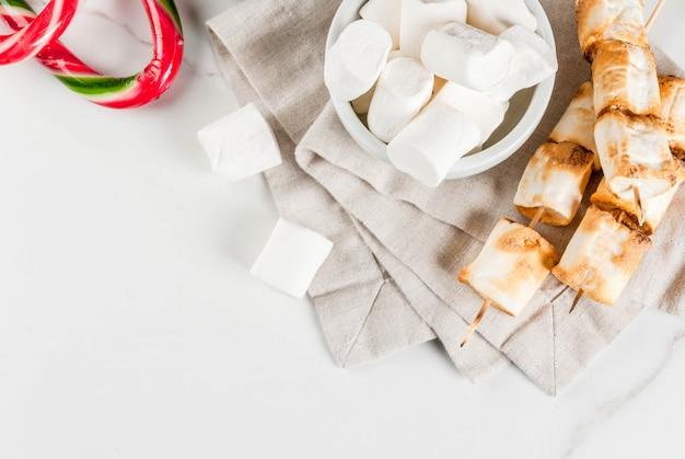 Bastão de doces doces tradicionais de natal, marshmallow e assado no espeto de marshmallow de fogo na vista superior branca, copyspace