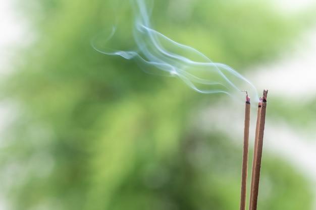 Bastão de incenso e fumaça da queima de incenso. fumaça bonita.