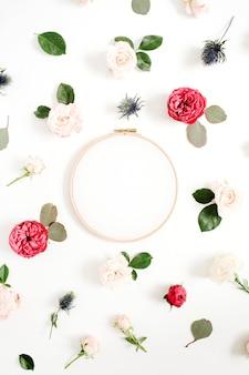 Bastidor de bordar com padrão de botões de flores rosa vermelha e bege em fundo branco. camada plana, vista superior