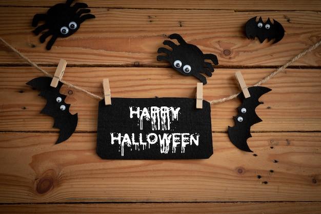 Bastões, aranha e teia de aranha no fundo da mesa de madeira com texto de feliz dia das bruxas.