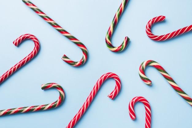 Bastões de caramelo de natal em um pastel azul. cartão celebração festiva de férias com copyspace para adicionar texto.