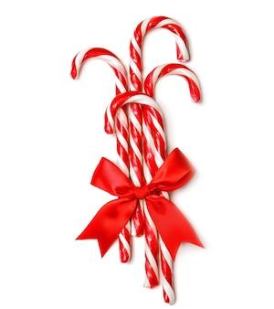 Bastões de doces com laço vermelho em fundo branco