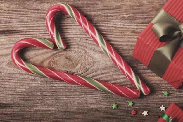 Bastões de doces como coração e presentes na placa de madeira