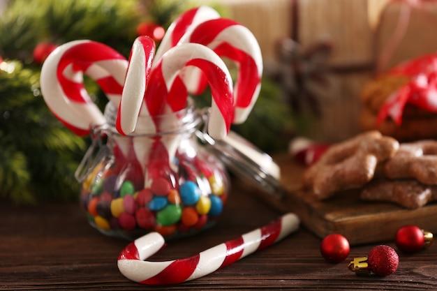 Bastões de doces de natal em uma jarra com decoração de natal na mesa com fundo brilhante