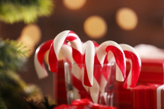 Bastões de doces de natal em vidro com decoração de natal na mesa com fundo brilhante