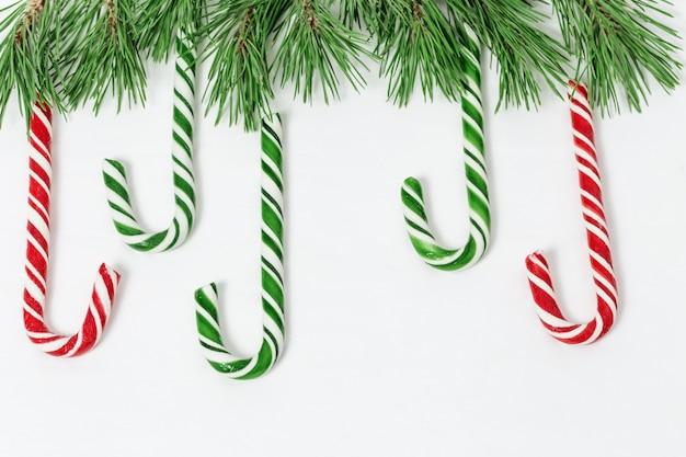 Bastões de doces de vermelho e verde com árvore de natal em fundo branco de concreto,