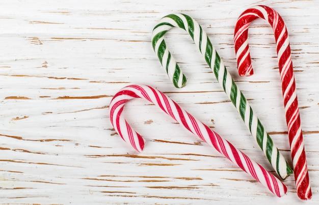 Bastões de doces decoração-coloridos do natal na tabela branca velha. ano novo.