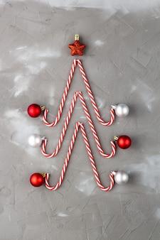 Bastões de doces em forma de árvore de natal com estrela e bola em fundo cinza. conceito abstrato do feriado de ano novo.