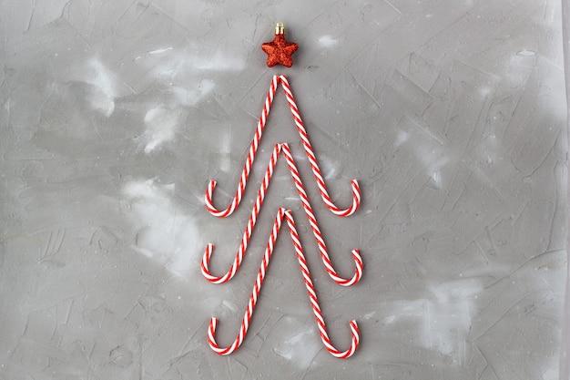 Bastões de doces em forma de árvore de natal e estrela em fundo cinza. conceito abstrato do feriado de ano novo.