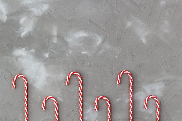 Bastões de doces vermelhos e brancos isolados em cinza