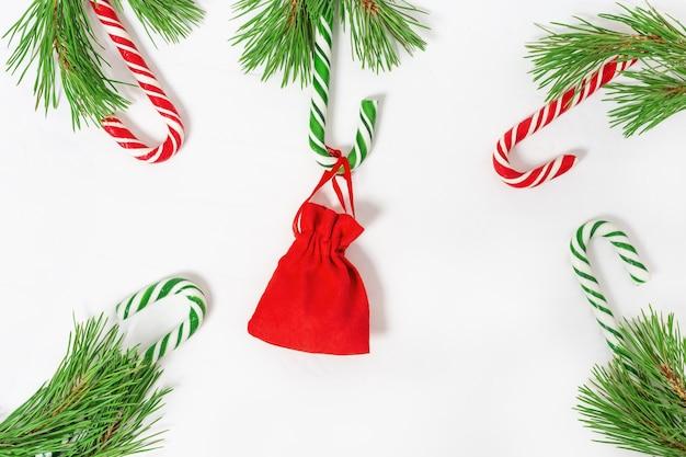 Bastões de doces vermelhos e verdes com pequeno presente, tema de natal.