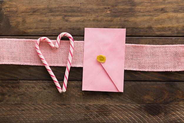 Bastões de fita, envelope e doces