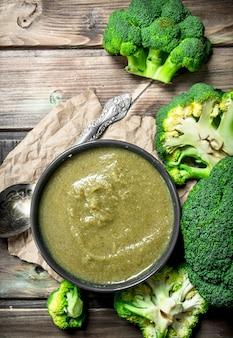 Bata os brócolis em uma tigela com uma colher. sobre um fundo de madeira.
