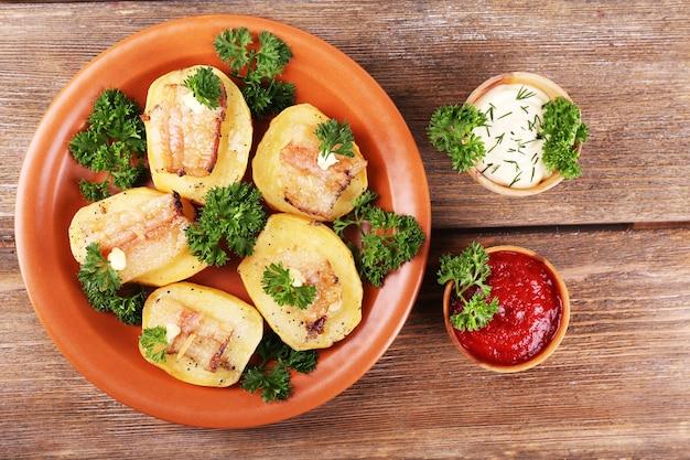 Batata assada com bacon no prato, em madeira
