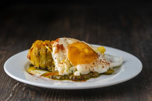 Batata assada com ovo frito em chapa branca na mesa de madeira, close-up