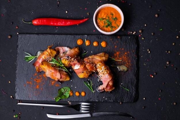 Batata assada em fatias de bacon com molho de mostarda e mel, em uma superfície escura