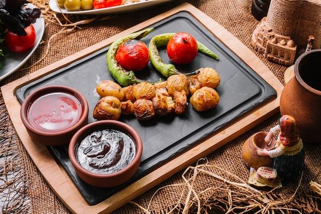 Batata assada na placa de madeira com vista lateral para molhos de tomate pimenta