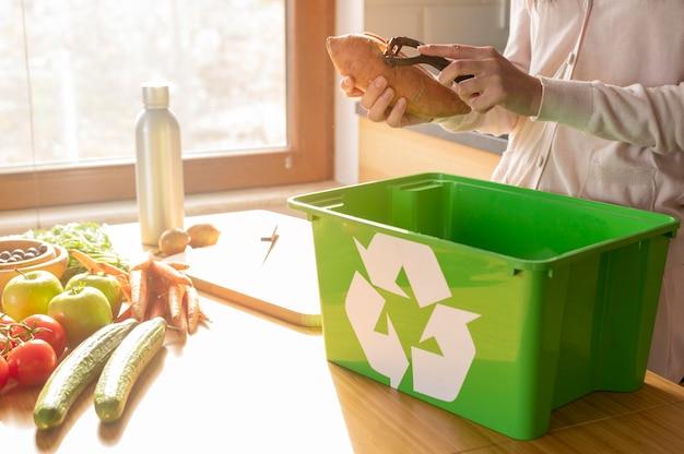Batata de casca de mulher na cesta de reciclagem