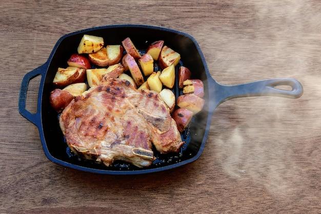 Batata de porco com carne de porco em uma batata com cebola branca rural em uma vila
