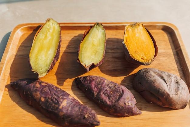 Batata doce cortada ao meio em um prato de madeira