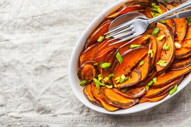 Batata doce cortada cozida com as cebolas verdes no prato branco.