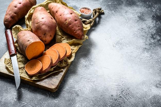 Batata-doce crua em uma tábua, inhame orgânico. fundo de legumes de fazenda