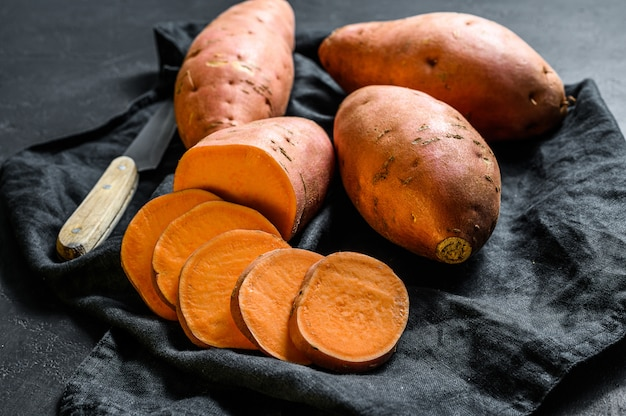 Batata-doce crua, inhame orgânico. a comida da fazenda. fundo preto.