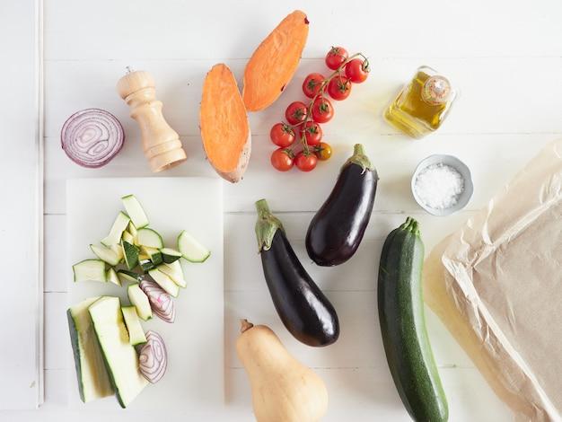 Batata-doce de vegetais crus diferentes, tomate cereja, abóbora e abóbora pronta para assar em uma receita vegan caseira