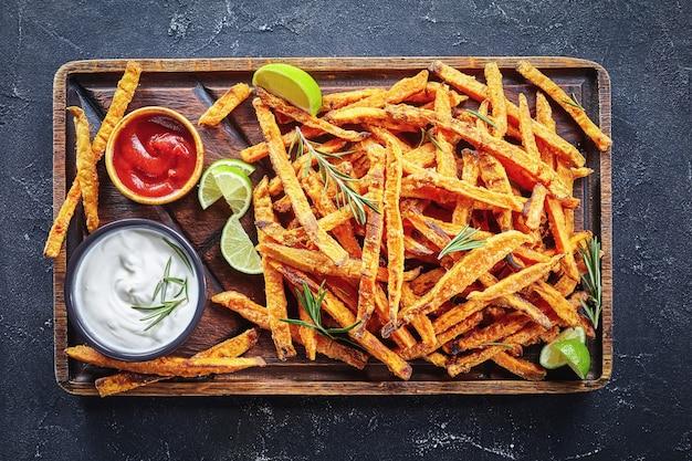 Batata doce frita com molho e ketchup em uma placa de madeira rústica sobre uma mesa de concreto com limão e buquê de ervas aromáticas