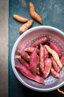 Batata-doce roxa em uma peneira de metal em um fundo escuro