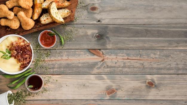 Batata e frango fast food na mesa de madeira