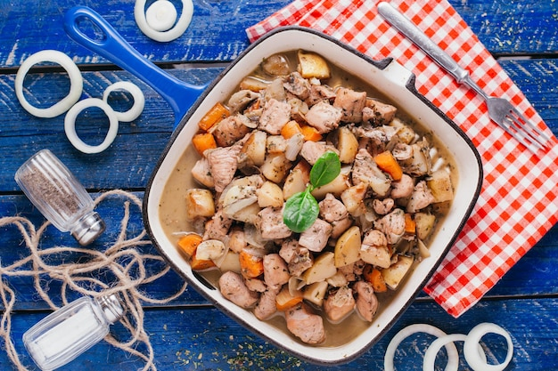 Batata estufada com carne e cenoura na mesa, prato de restaurante em vista superior do fundo de madeira