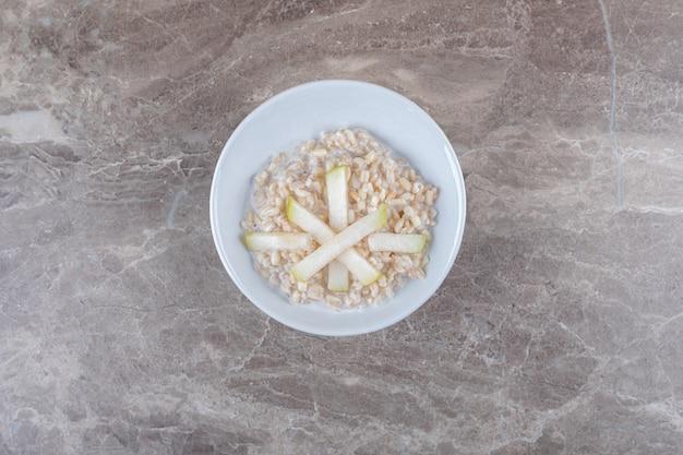 Batata fatiada em um prato de arroz, na superfície de mármore