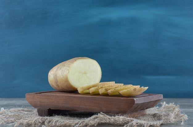 Batata fatiada em uma travessa, no tripé, na mesa de mármore.
