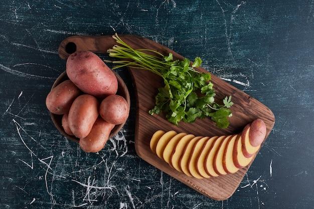 Batata fatiada na placa de madeira com salsa.