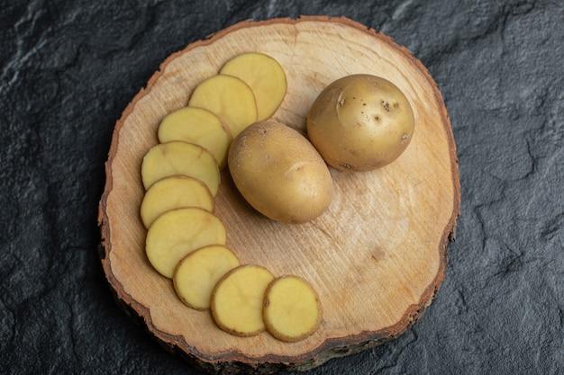 Batata fatiada ou inteira em uma placa de madeira marrom
