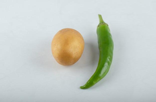 Batata fresca e pimenta verde em fundo branco.