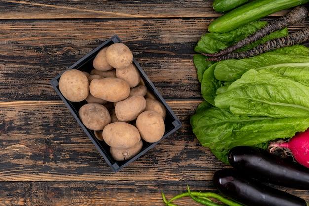 Batata fresca na cesta preta, com legumes na mesa de madeira