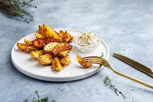 Batata frita com molho de ervas, tomilho e queijo, servido no prato de cerâmico branco com garfo e faca de ouro e guardanapo dourado.