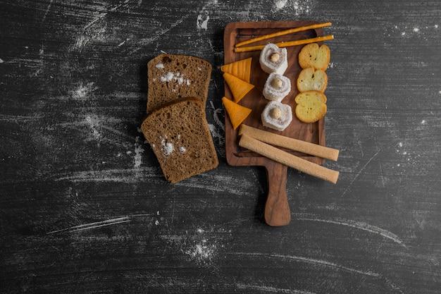 Batata frita com produtos de confeitaria em travessa de madeira servida com pão preto