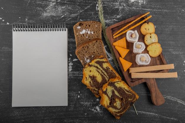 Batata frita com produtos de confeitaria em uma travessa de madeira e fatias de pão à parte com um livro de recibos